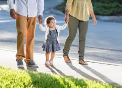 Hispanic toddler walking with parents