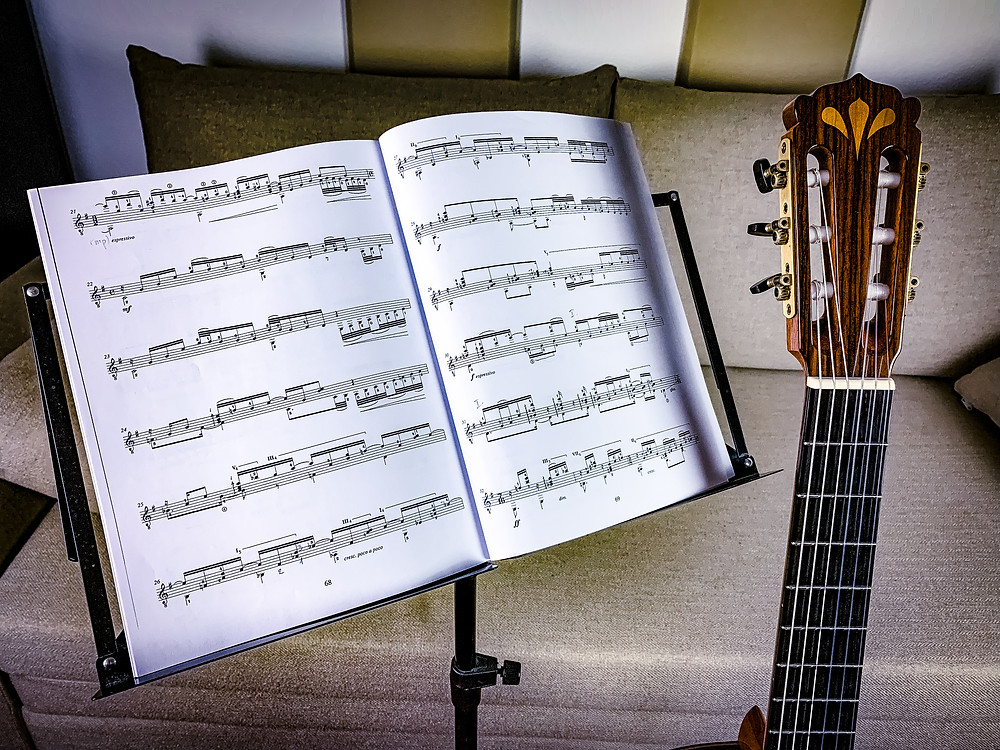 Classical guitar with guitar music on a note stand