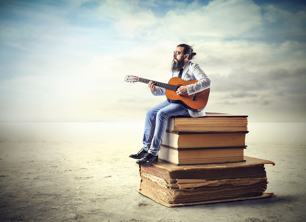 Man with a guitar sitting on a pile of books