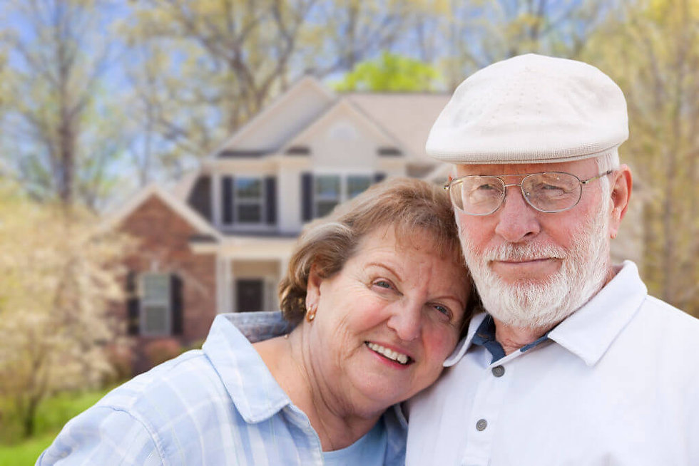 happy-senior-couple-in-front-yard-of-hou