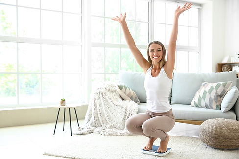 Happy young woman on scales at home. Weight loss concept.jpg