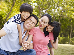 An Asian-American family poses for a photo in a park after receiving gifted evaluations and twice exceptional (2e) evaluations for their children around Phoenix and Scottsdale, Arizona.