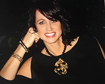 Image shows Theresa Harnois. She is a behavioral specialist posing for a headshot wearing a black top and a gold pedant necklace smiling invitingly.