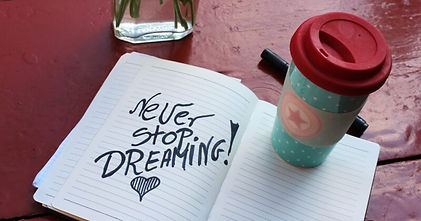 An open book with the words - never stop dreaming
