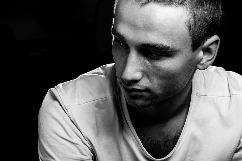 Melancholic guy on dark background. Face