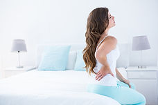 Attractive woman with back pain at home