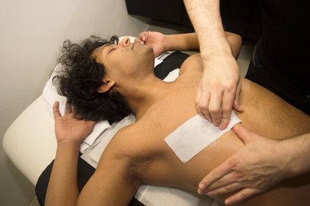 Male Waxing (upper chest) Arms stretched out to stretch out the skin on the chest.