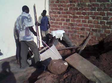 Versenken der schweren Betonschächte in den 2m tiefen Gruben; sie dienen als Zwischenpunkte beim Verlegen der Kabel
