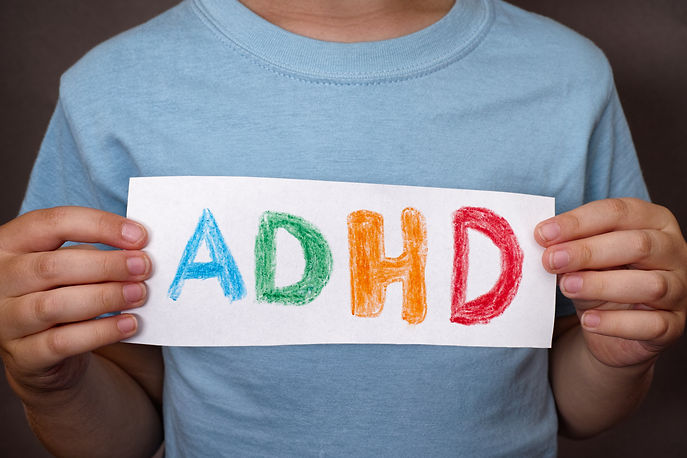 Young boy holds ADHD text written on she