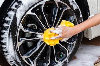 mano-mujer-esponja-amarilla-lavado-rueda