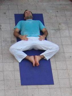 Man doing the Supta Baddha Koṇāsana pose
