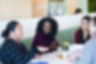 women of color talking around table