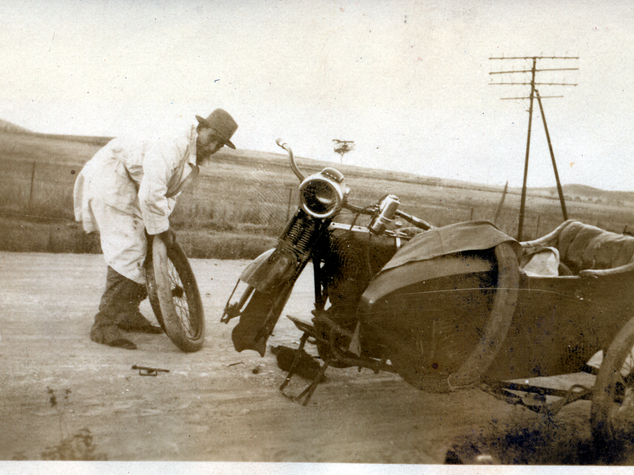 Ben changing flat tyre on motorcycle c 1925