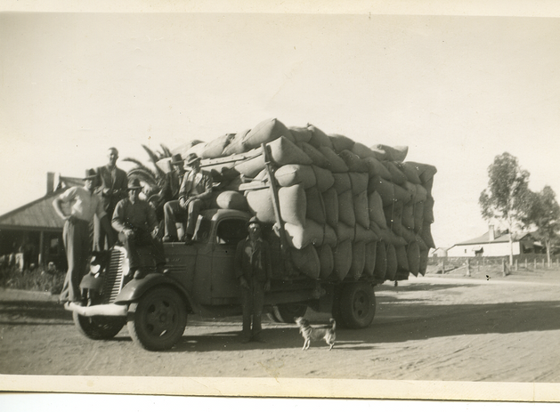 Truck loaded with bags of wheat and six blokes