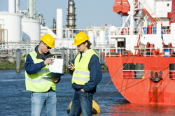 Two harbor workers going over docking plans in at a petrochemical port