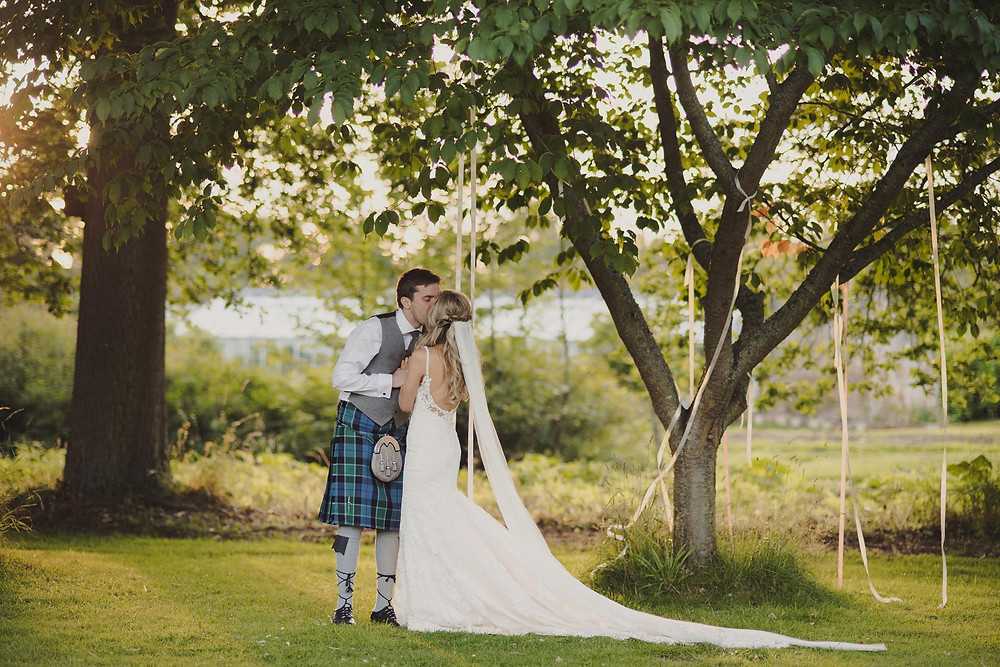 East Lothian Wedding at Colstoun with a beautiful couple kissing under a tree, photo property of Anna Urban Wedding Photography