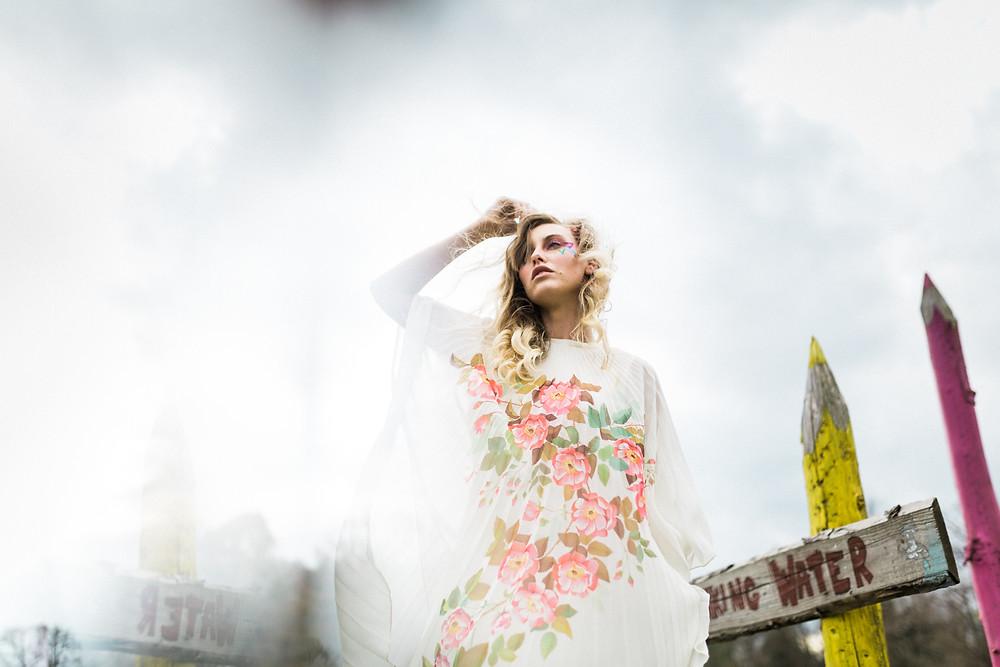 alternative bride in vintage floral wedding dress next to sign