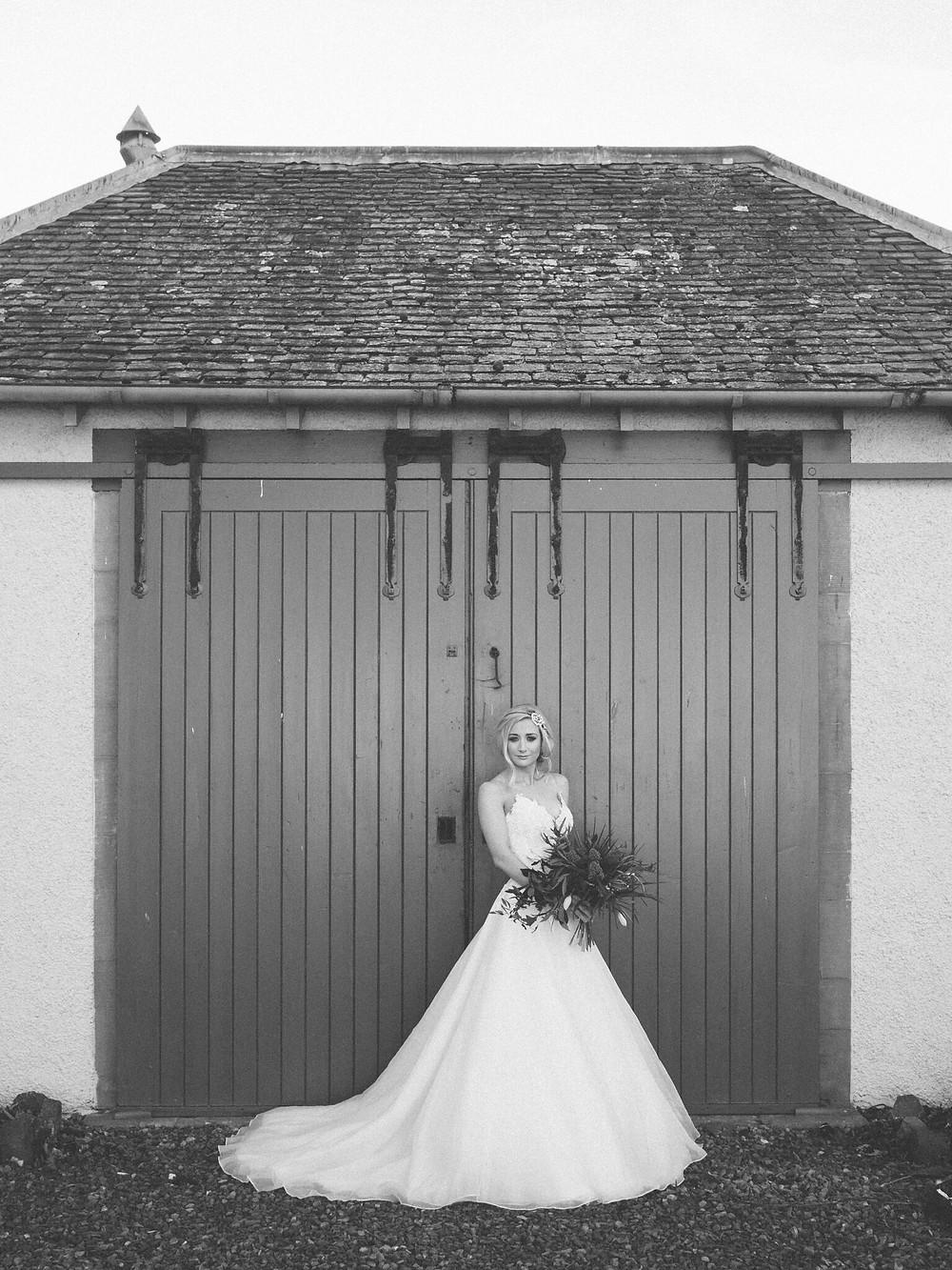 Black & White Photo of Bridge in White Dress holding Boquet