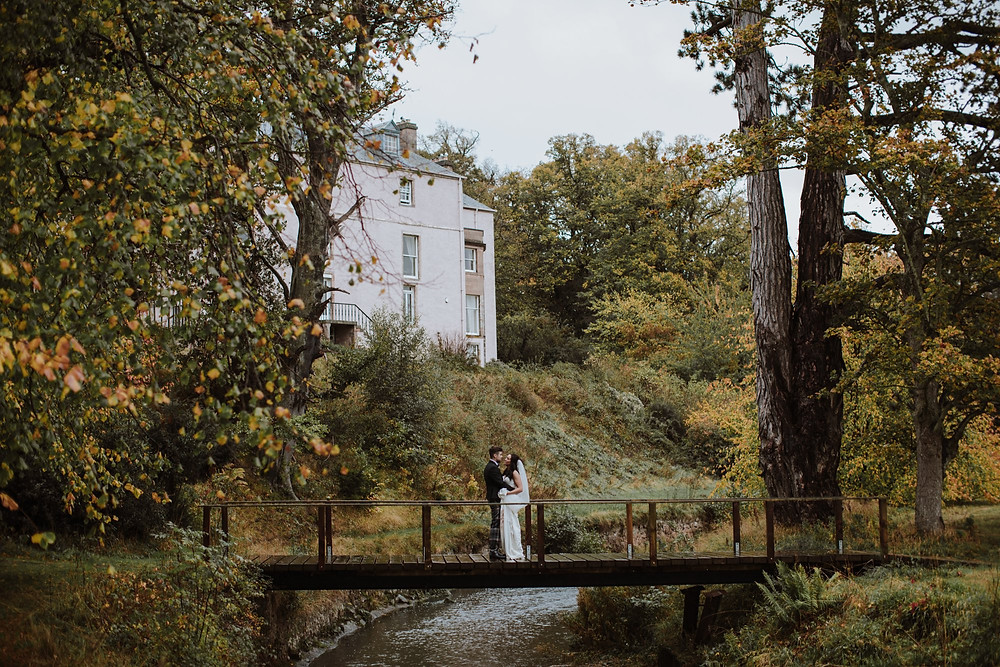 Autumnal Scottish Wedding Scene on Bridge in front of Castle