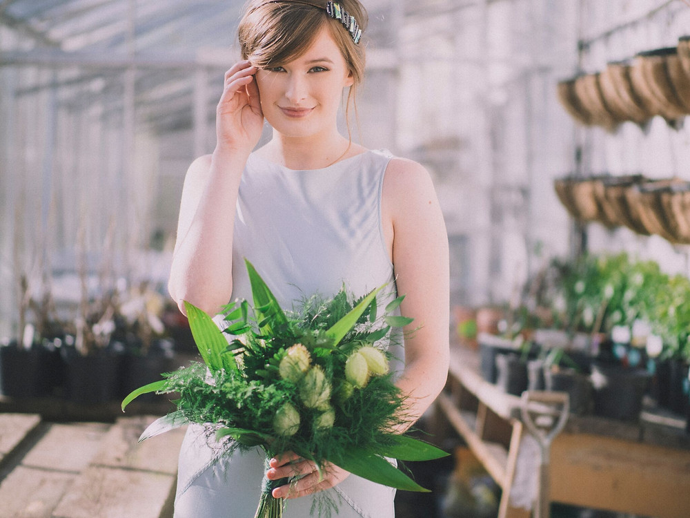 Bridesmaid holding Boquet wearing a long dress with headpiece in glasshouse