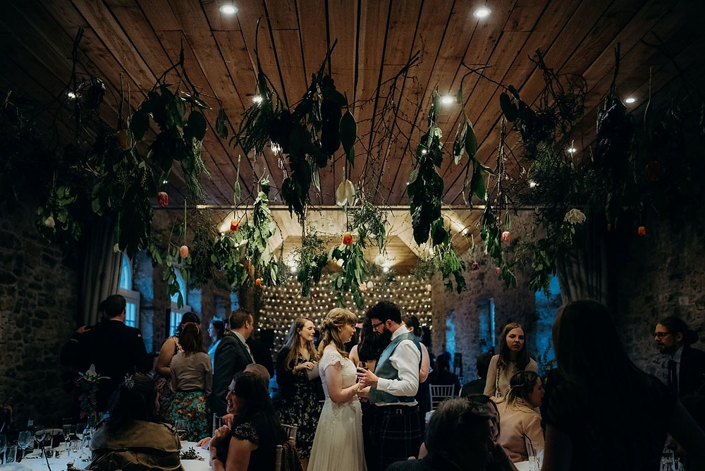 Barn Wedding Scotland. Hppily Married couple standing holding hands and dancing in an East Lothian Wedding barn. photo property of Fiona Higgins Photography