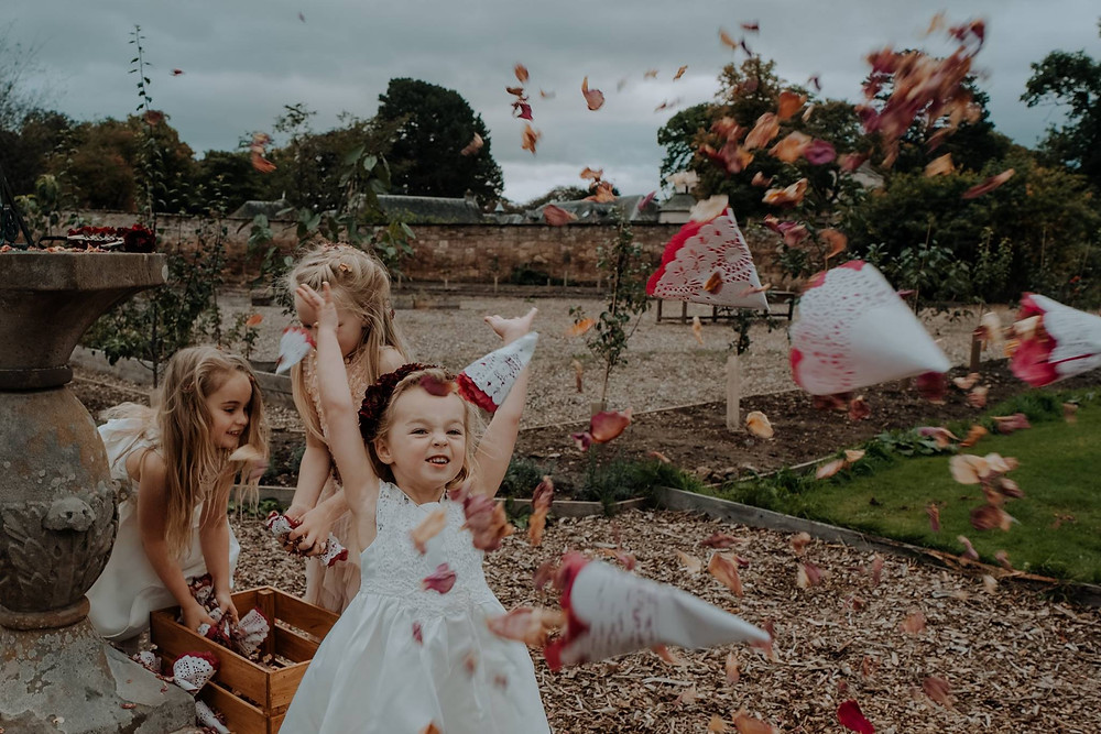 Children at wedding playing with confetti having a fun time during a wedding at Colstoun East Lothian Scotland. Photo property of Christine McNally