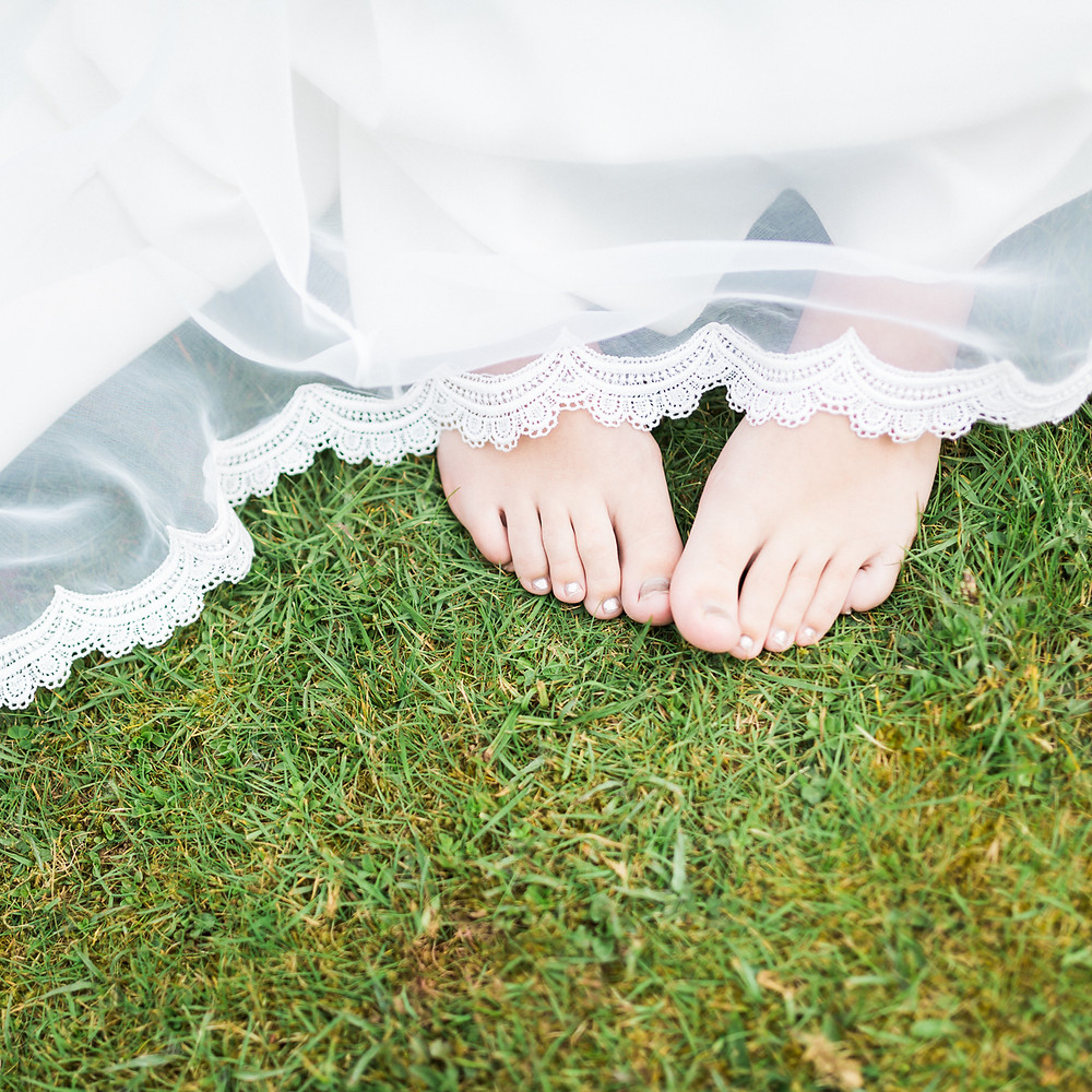 wedding dress and bare feet standing on grass