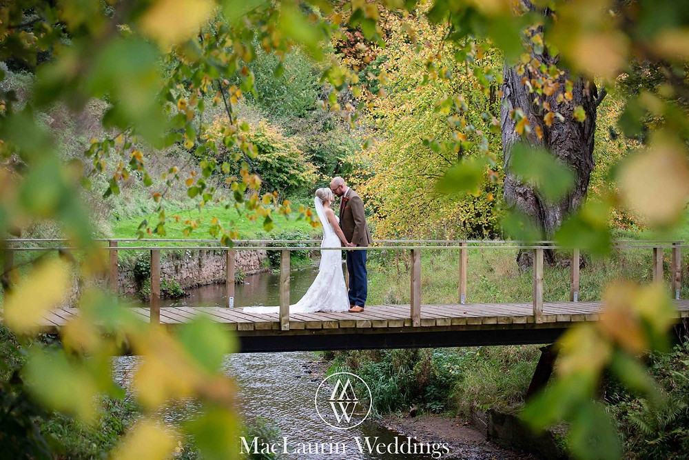Couple lovingly embracing on a bridge Colstoun East Lothian Scotland - Photo property of MacLaurin Weddings
