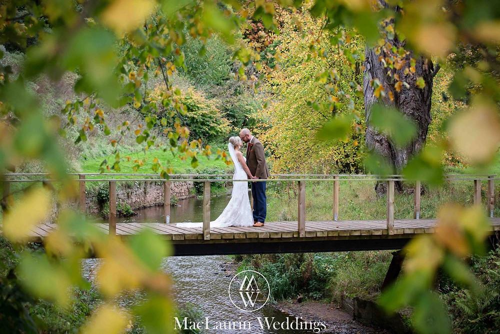 Couple lovingly embracing on a bridge Colstoun East Lothian Scotland - Photo property of MacLaurin Weddings