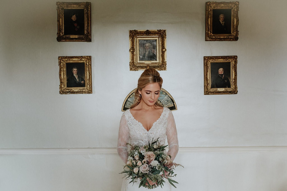 Bride Standing in front of portraits in front of Scottish Castle