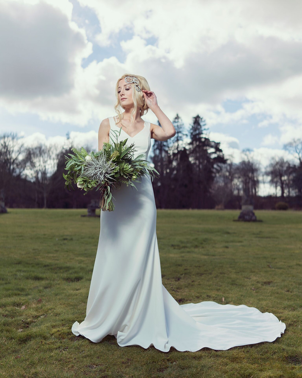 bride standing on west lawn with boquet and large crystal headpiece
