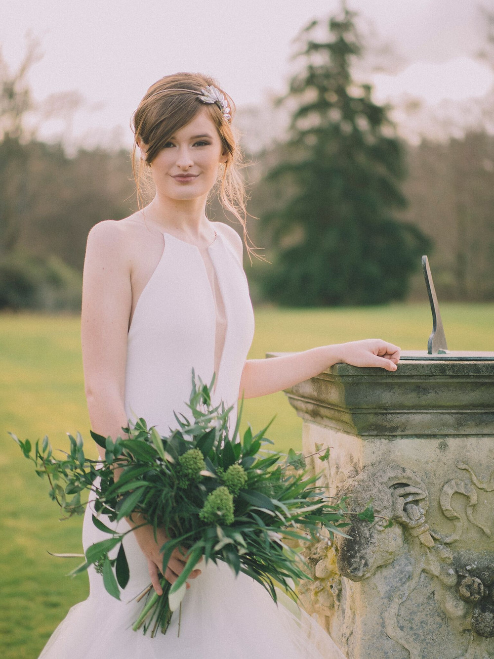 Bride Holding boquet on the west lawn, next to a sun dial wearing beautiful headpiece