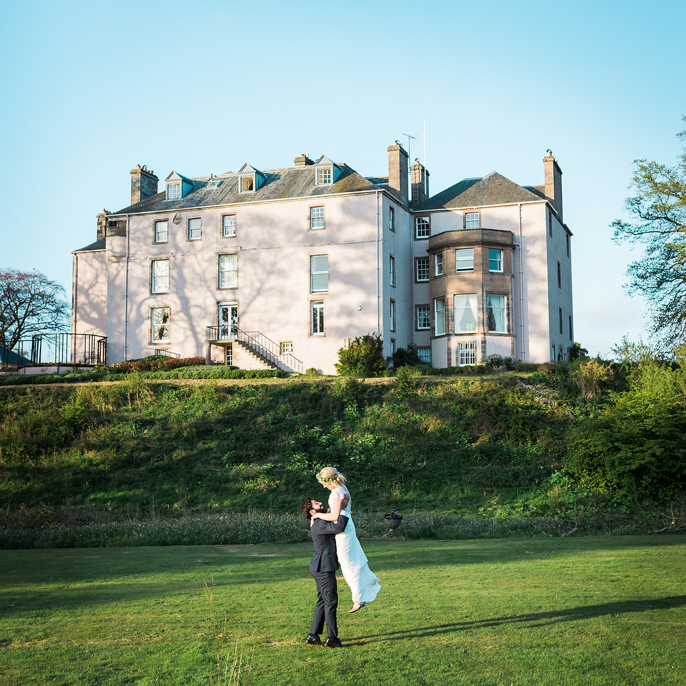 newly married couple dancing in front of Colstoun House