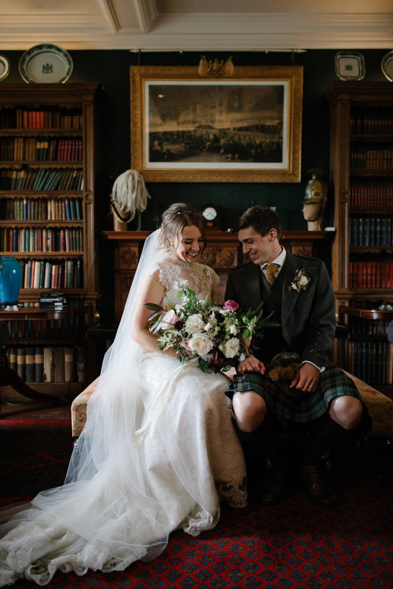 Scottish Country House Wedding, a beautiful couple sitting in the library at Colstoun East Lothian. photo property of Caro Weiss Photography