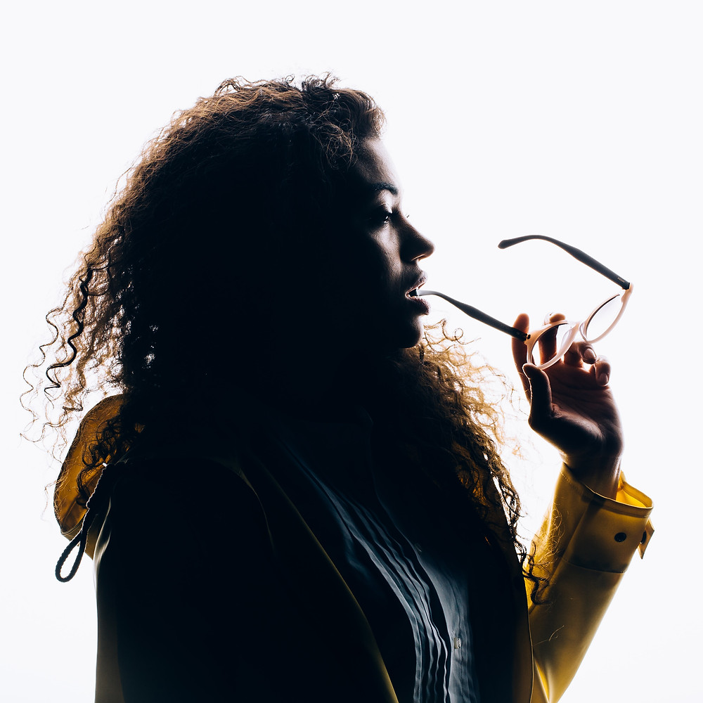 silhouette of a woman biting her eyeglasses