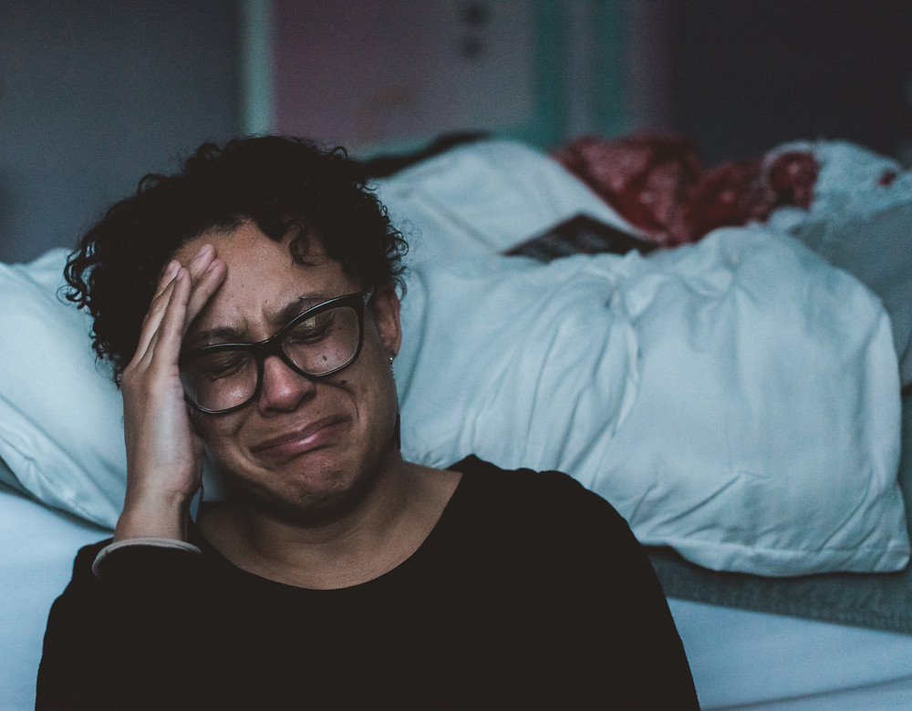 brown skinned woman crying beside her bed