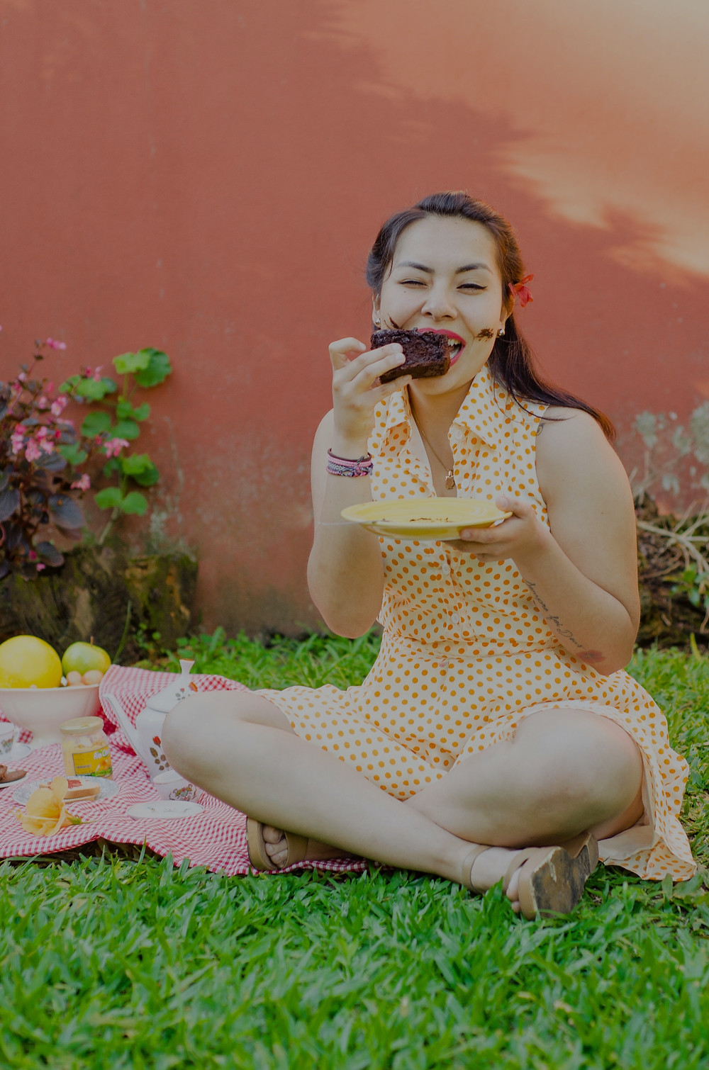 woman crossed-legged, sitting at a picnic, eating a brownie