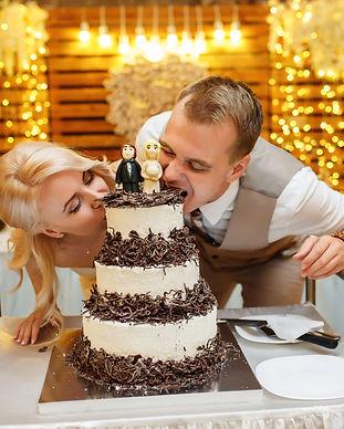 Wedding cake. Bride and groom bite cake.