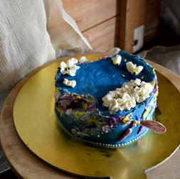 A pastel colored asymmetric cake set in the tones of deep blue and white .  Cake guts - Chocolate x Caramel x Dulce de leche
