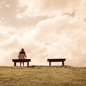 a women sitting alone on a bench waiting