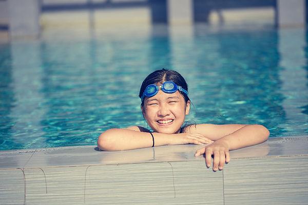 プールで泳いで幸せな女の子