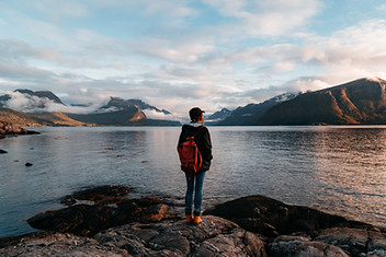Girl stadning on rock looking at ocean and mountains