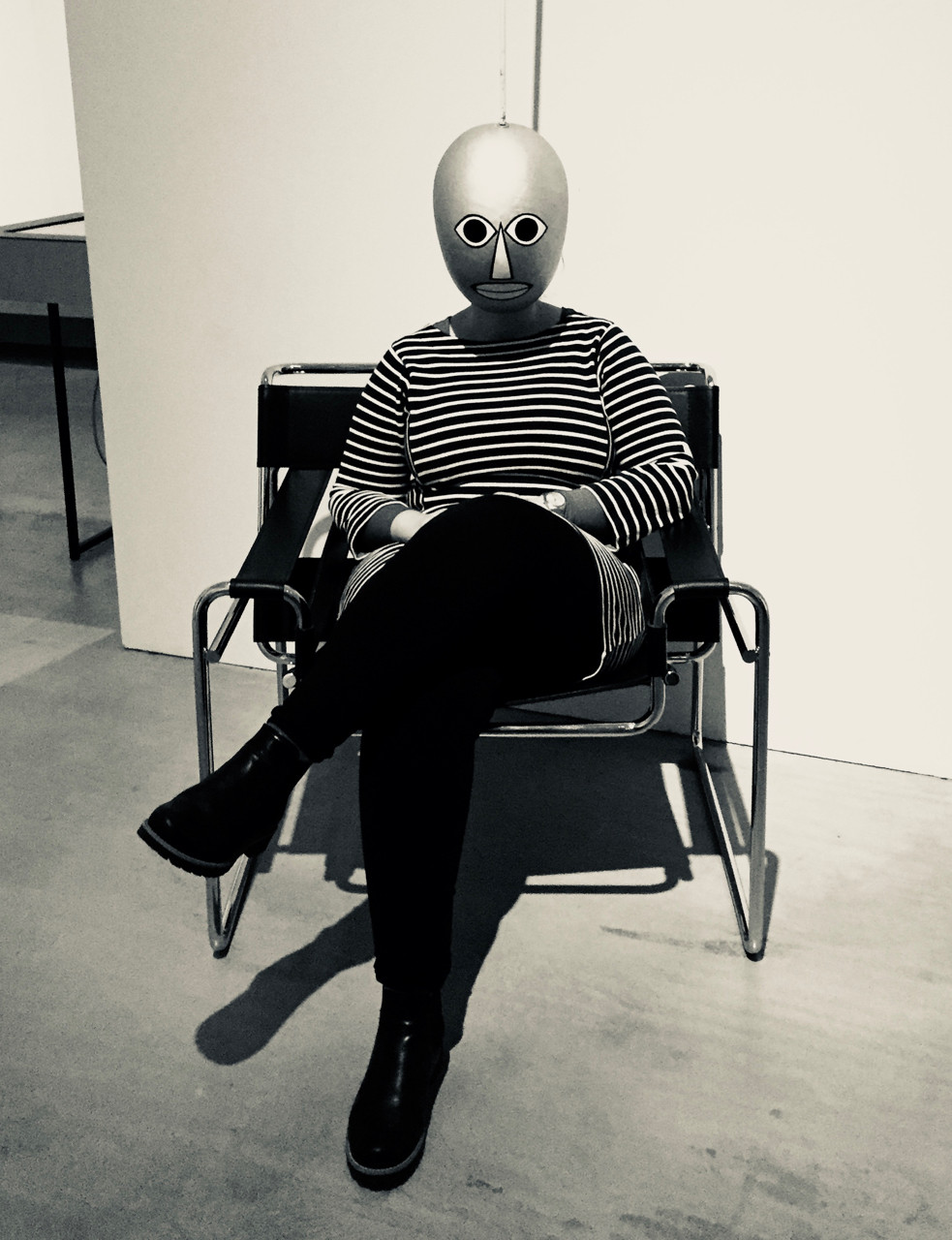 Masked woman sitting in a modernist chair.