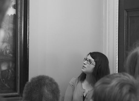 Alexandra Chiriac talking about a painting in font of audience.