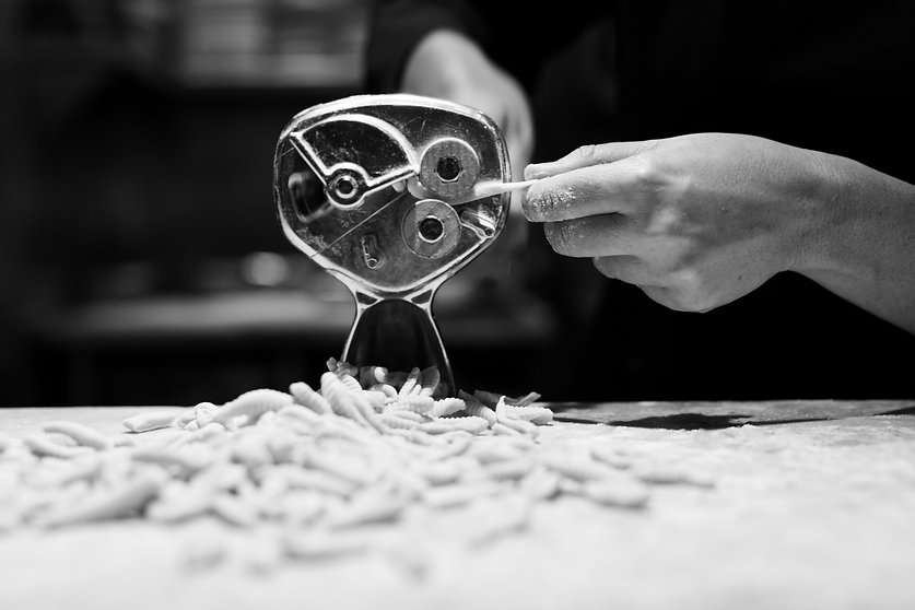 Black and white photo of chef making pasta in the kitchen