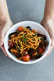 Hands holding seafood pasta dish