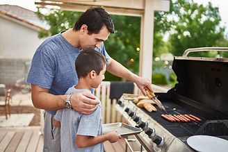 father teaching son how to grill hot dog