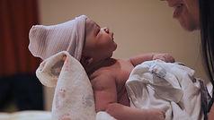 newborn baby stares into moms eyes