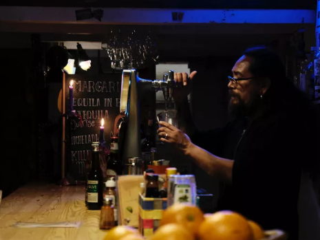 bartender pouring drink in a dive bar