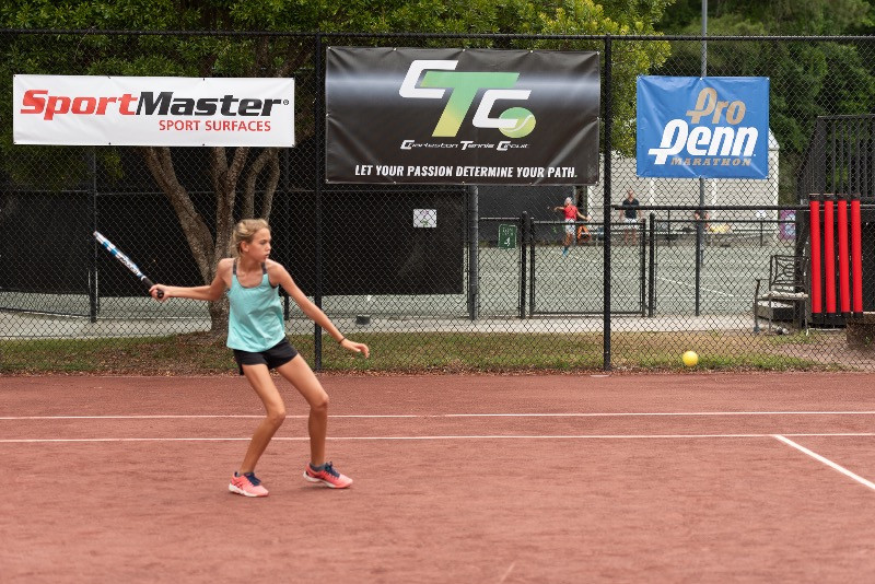 CTC particpant hits a great forehand and sponsor logos of SportMaster and CTC are in the background.